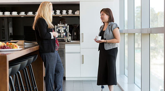 Two women facing each other in a kitchen holding cups having a conversation